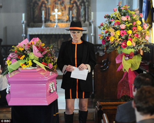 Shirley Carter standing by heather trotts coffin in eastenders bbc